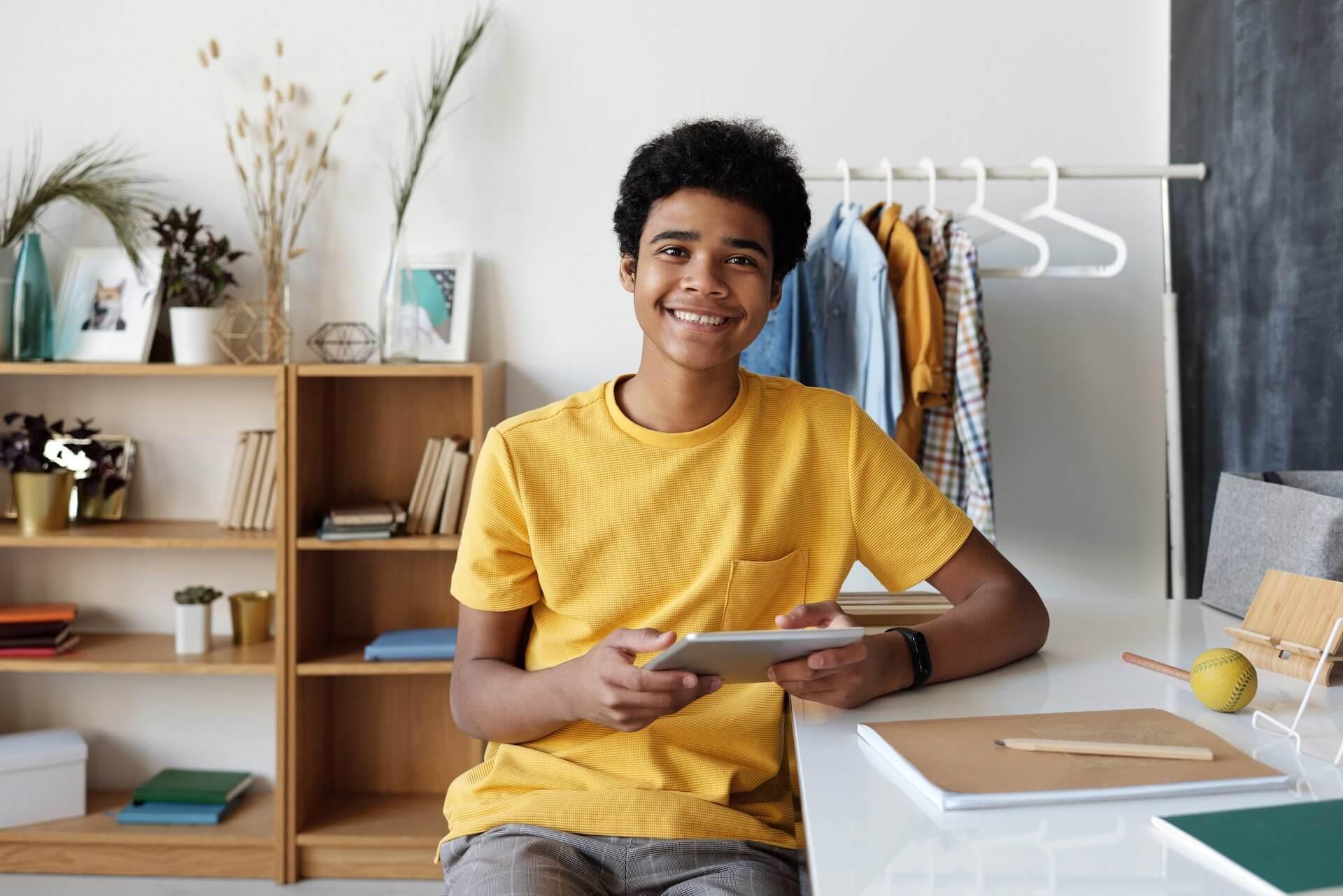 Kid smiling holding iPad